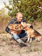 Young man with his dog on sunny autumn forest glade with mushrooms Stock Photos