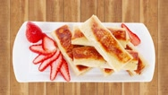 Pancake with various fillings served over old style wooden table Stock Footage