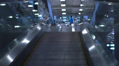 People moving on flat escalators in a airport terminal or train station. Slow Stock Footage