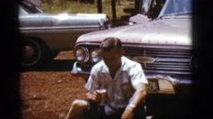 1968: man sitting on ground in front of car takes relaxed sip of canned beverage Stock Footage