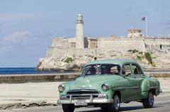 Vintage american cars alomg the Malecon, behind is Morro Castle, a picturesque Stock Photos