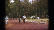1968: a man and woman walking up the path along a beautiful park with pine trees Stock Footage