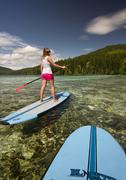 A young paddle boarder looks back at her partner while navigating across the Stock Photos