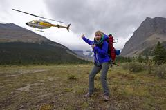 A young lady is excited to be dropped off near Berg lake on Mount Robson, just Stock Photos