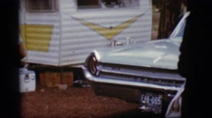1968: a couple outside walking past a car towards a recreational vehicle Stock Footage