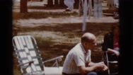 1968: three persons sitting and having a talk outside a vehicle COTTONWOOD, Stock Footage