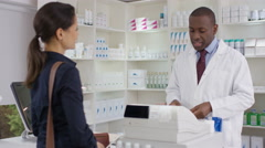 4K Friendly pharmacy worker serving customers & taking payment at the till Stock Footage