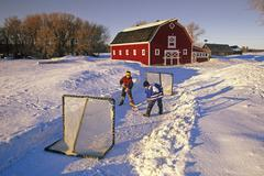 Boys playing hockey in front of a red barn , near Oakbank, Manitoba, Canada Stock Photos
