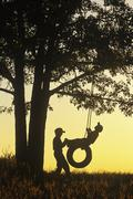 Boys playing on tire swing under oak tree, Birds Hill Provincial Park, Manitoba, Stock Photos