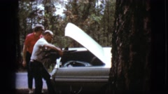 1968: a middle aged man helps young woman by placing firewood in her vehicle's Stock Footage