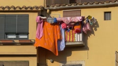 Clothes hanging on a colourful facade in the wind Stock Footage