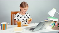 Girl 7-8 years applying jam to bread with butter sitting at the table Stock Footage