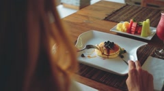 Blueberry pancakes, fruits, juice and coffee on wooden table Stock Footage