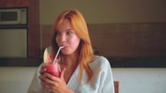 Girl drinking juice, looking around playfully Stock Footage
