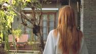 Young woman walking in bath robe? towards door of villa Stock Footage