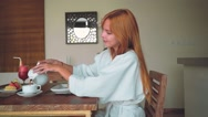 Young woman having breakfast: pouring coffee into cup Stock Footage