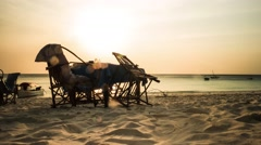 Sunset view of pub table and chairs on african beach, timelapse Stock Footage