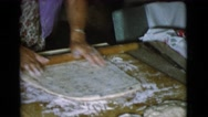 1968: a woman with a wooden dowel is shaping dough for making bread  Stock Footage