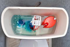 Flush mechanism inside cistern of toilet, blue water tablet dissolves. Kuvituskuvat