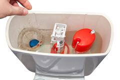 Hand throws blue cleaner tablet in flush tank toilet bowl. Stock Photos