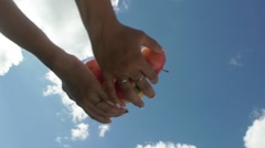 Female hand throw up apples on a background of blue sky. Slowmotion Stock Footage
