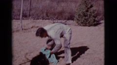 1968: man plays with dog by rubbing it with a blue towel outside COTTONWOOD, Stock Footage