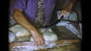 1968: a woman is using a big knife to cut a big portion of fresh dough  Stock Footage