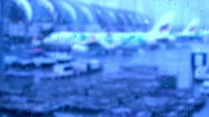 Raindrops on the window of airport terminal with blur airport outside Stock Footage