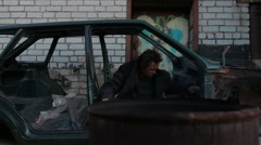 A homeless man sitting in old car Stock Footage