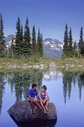 A couple relaxes by Harmony Lake, Whistler mountain on a sunny summer evening. Stock Photos