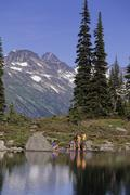 A group of hikers relax by Harmony Lake, Whistler Mountain, BC on a sunny summer Stock Photos