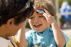 A toddler giggles with his Dad as he lifts sunglasses above his forehead. Stock Photos