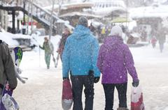 A couple enjoys strolling and shopping Whistler village on a winter day. Stock Photos