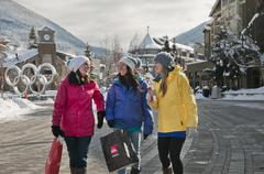 A trio of women shop Whistler Village on a winter day. Stock Photos