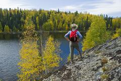 Hiker on Precambrian shield rock, Dickens Lake, Northern Saskatchewan, Canada Stock Photos