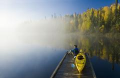 A man on dock with kayak, Dickens Lake, Northern Saskatchewan, Canada Stock Photos