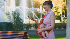 Young woman with sleeping baby in sling tells about amazing event Stock Footage