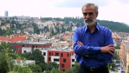 Old senior man smiles to camera with folded arms - city (buildings)  Stock Footage