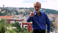 Old senior man shows thumb up on agreement - city (buildings) in background Stock Footage