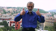 Old senior man shows thumbs up on agreement - city (buildings) in background Stock Footage