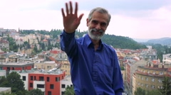 Old senior man waves with hand - city (buildings) in background Stock Footage