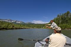 Middle-aged man fly-fishing on Elk River with guide rowing fishing boat, near Kuvituskuvat