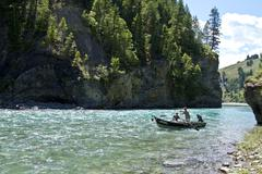 Middle-aged man fly-fishing on Bull river with guide rowing fishing boat, East Kuvituskuvat