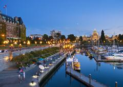 The Inner Harbour of Victoria is a picturesque walkway along the water, framed Stock Photos