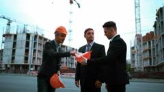 Engineer giving businessmen helmets Stock Footage