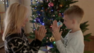 Mom and son clapping and smiling under christmas tree happy family Stock Footage