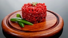 Raw hamburger cutlet with sprouts and chilli pepper on wooden pl Stock Footage
