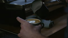 Barista pouring milk into coffee Stock Footage