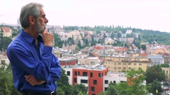 Old senior man walks and thinks about something - city (buildings) in background Stock Footage