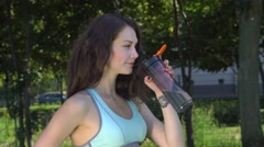 Beautiful girl drinking from a bottle of water after workout Stock Footage